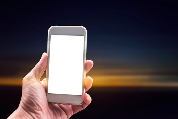 Closeup of hand using mobile with blank screen at sunset background.