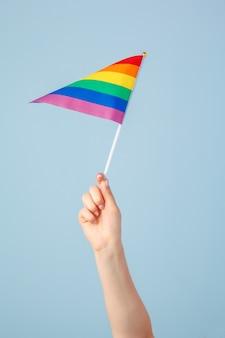 Closeup of a hand waving a small rainbow flag