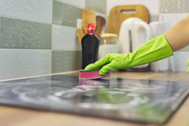 Closeup of hand woman cleaning modern cooking glass ceramic electric surface with sponge and detergent