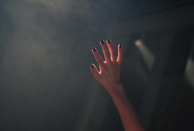 Primo piano della mano di una donna che copre le luci con uno sfondo sfocato scuro