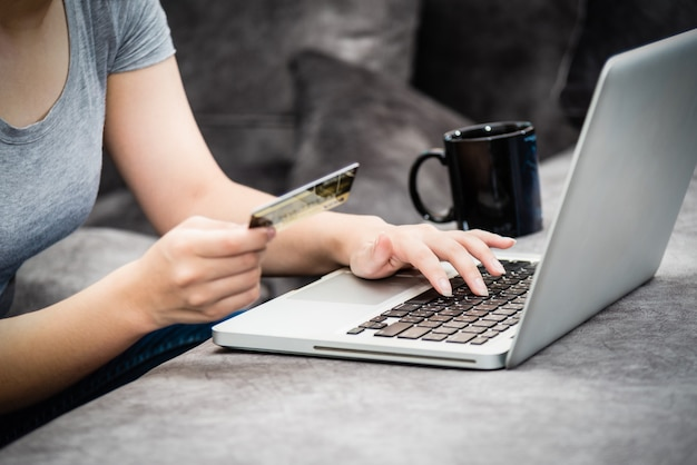 Closeup hand of woman holding sme credit card and using keyboard laptop computer to buy products payment shopping online, spend money, e-commerce, internet banking, working remotely from home concept