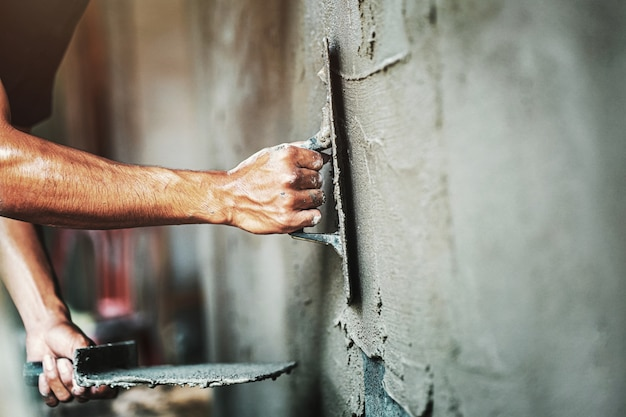 Closeup hand of worker plastering cement at wall for building house Premium Photo