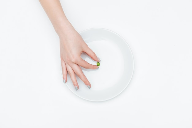 Closeup of hand of young woman taking one small green pea from the plate