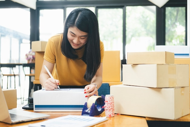 Closeup hand of young woman writing address on parcel box  for delivery order to customer, shipping and logistic, merchant online and seller, business owner or sme, online shopping.