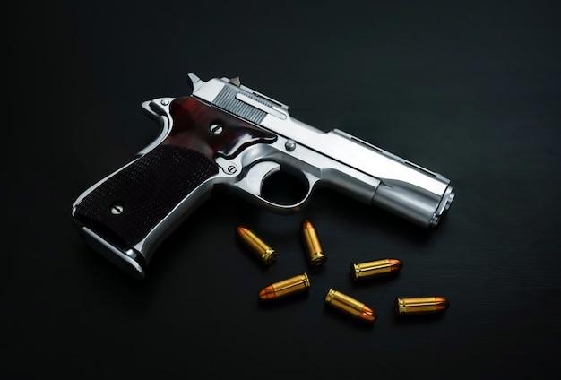 黒い表面に金色の鋭い弾丸が付いたクローズアップ拳銃