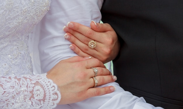 Closeup of hands bridal couple with wedding rings on nature background