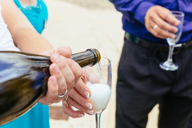 Closeup hands of the bride and groom with glasses of champagne wedding champagne glasses