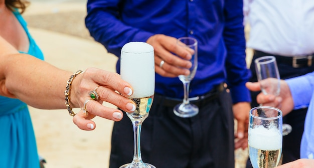 Closeup hands of the bride and groom with glasses  champagne