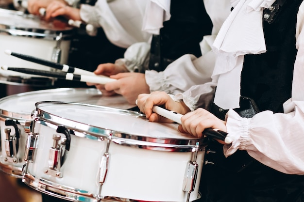 A closeup of the hands of a drummer at a parade. children's ensemble in white shirts. white new snare drum, white sticks. the concept of a military parade and march.