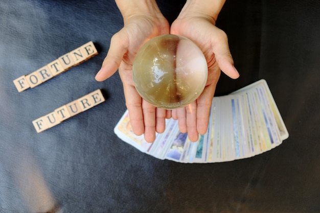 Closeup hands of fortune teller who show clear marble ball for prediction fate on tarot card
