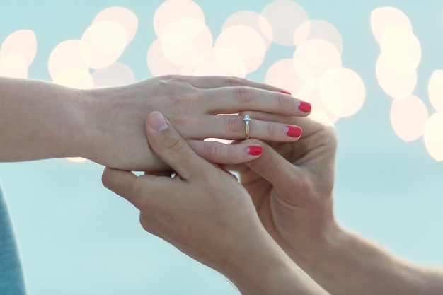 Closeup hands. the guy makes the girl a marriage proposal at evening in sand desert.