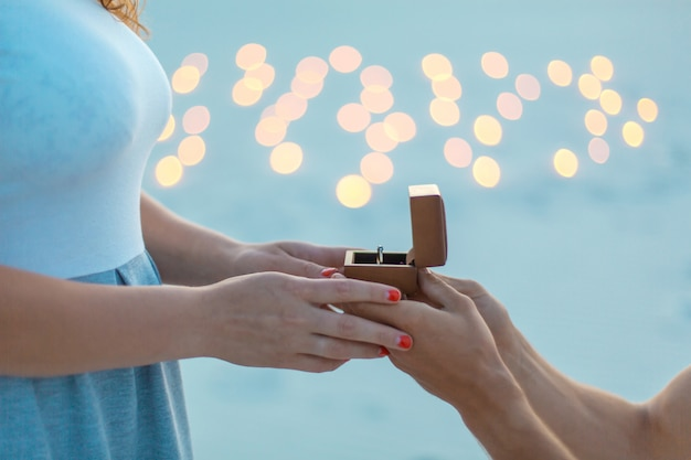 Closeup hands. the guy makes the girl a marriage proposal at evening in sand desert