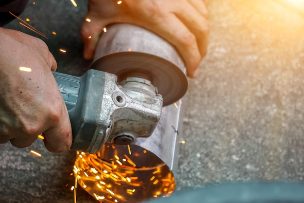 Closeup hands of laborer holding electric angle grinder working cutting galvanized pipe at construction site with sun flare background.