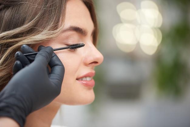Closeup of hands of makeup artist applying mascara in salon