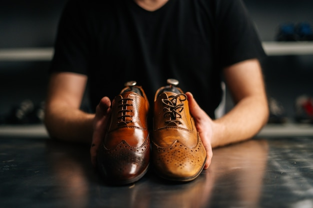 Closeup hands of male shoemaker holds old light brown leather shoe and repaired shiny shoes after re...