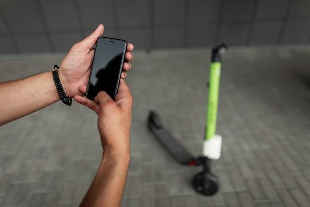 現代の携帯電話を持つ若い男のクローズアップの手。