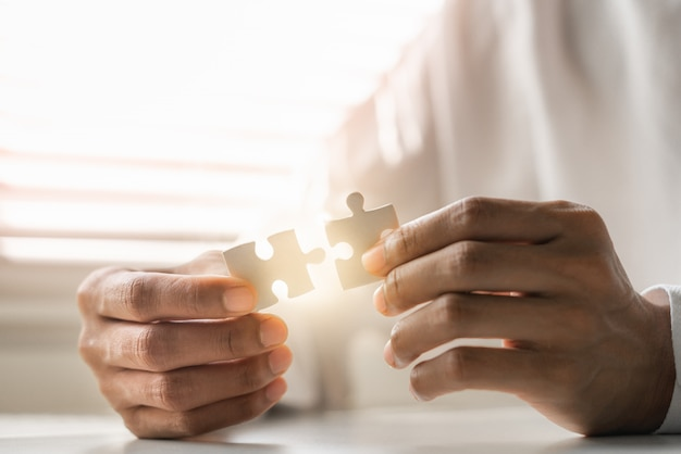 Руки крупного плана бизнесмена соединяя мозаику.
