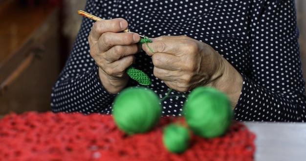 自宅でシニアニットを編む年配の女性のクローズアップの手