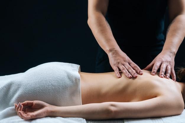 Крупным планом руки мужского массажиста делают массаж спины расслабленной молодой женщине в спа-салоне
