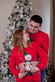 クリスマスの新年に幸せな妊娠中の女性と彼女の夫の形の心のクローズアップの手