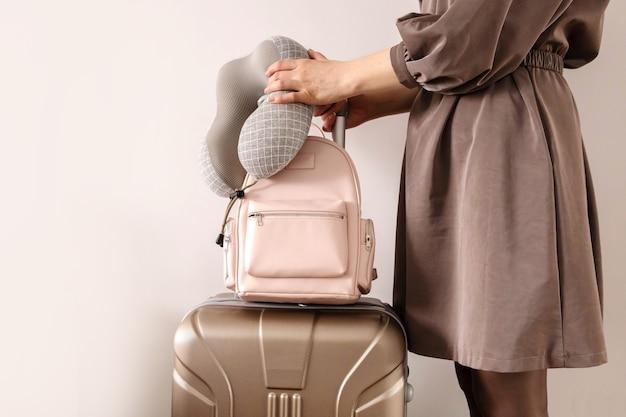 Крупным планом руки туристической женщины, держащей рюкзак и стильный чемодан, готовый к командировке в отпуск