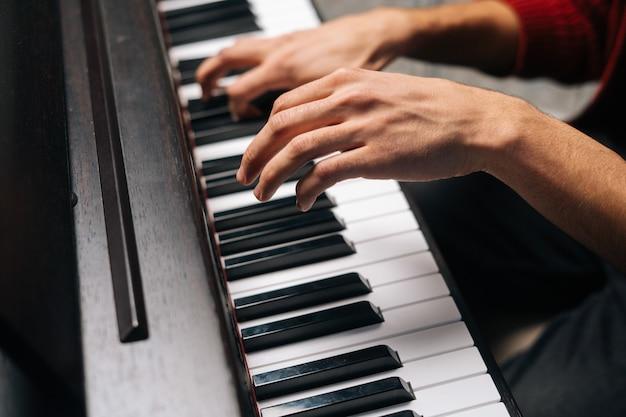 홈 녹음 스튜디오에서 피아노를 연주하는 알아볼 수 없는 남자의 클로즈업 손