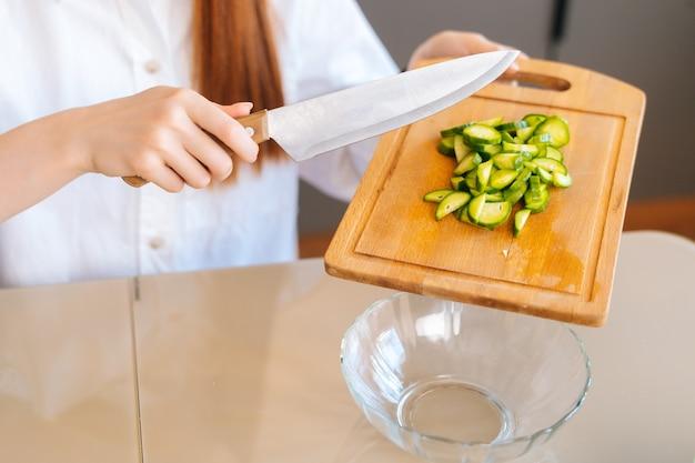 Крупным планом руки неузнаваемой женщины, бросающей нарезанные огурцы в стеклянную миску в современной кухонной комнате