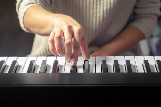 Closeup of hands playing piano.