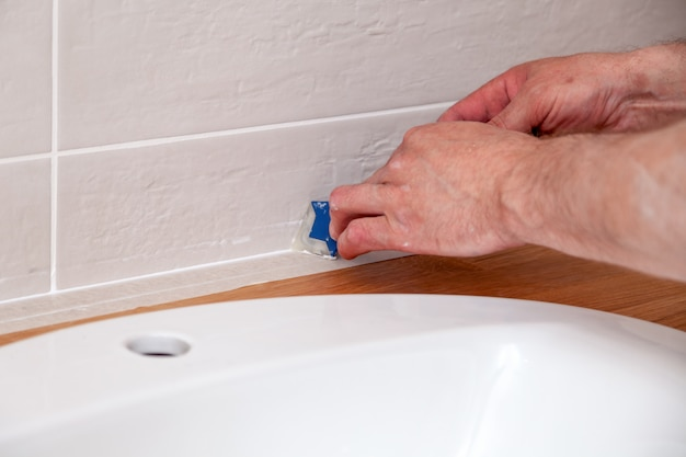 Closeup hands of professional plumber worker applying white sealant, joint compound, caulk to joint of wooden table top, beige tiled wall with rectangular tile using blue scraper
