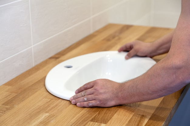 Closeup of hands of professional plumber worker installs white oval ceramic sink on wooden table top in bathroom with beige tile
