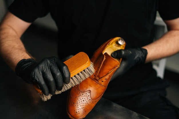 Closeup hands of shoemaker in black gloves polishing light brown leather shoes with brush during res...