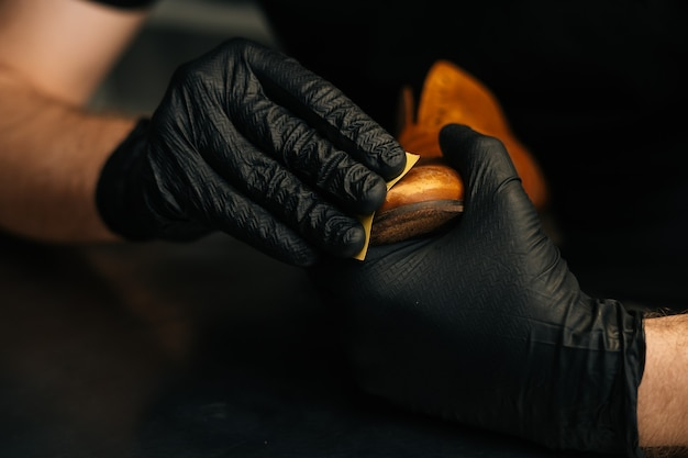 Closeup hands of shoemaker wearing black latex gloves rubbing old light brown leather shoes for late...