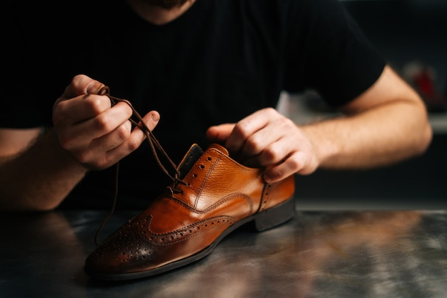 Closeup hands of unrecognizable male shoemaker tying laces on repaired and polished light brown leat...