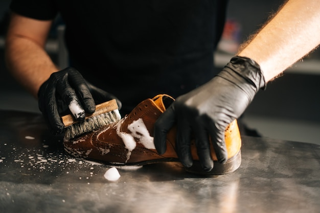 Closeup hands of unrecognizable shoemaker in black gloves applying cleaning foam on old light brown ...