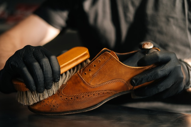 Closeup hands of unrecognizable shoemaker cleaning with brush old light brown leather shoes