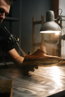 Closeup hands of unrecognizable shoemaker wearing black gloves spraying paint of light brown leather...