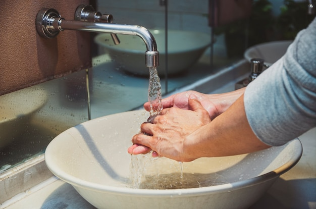 クローム蛇口とコロナウイルスパンデミック予防のための水で洗うクローズアップの手