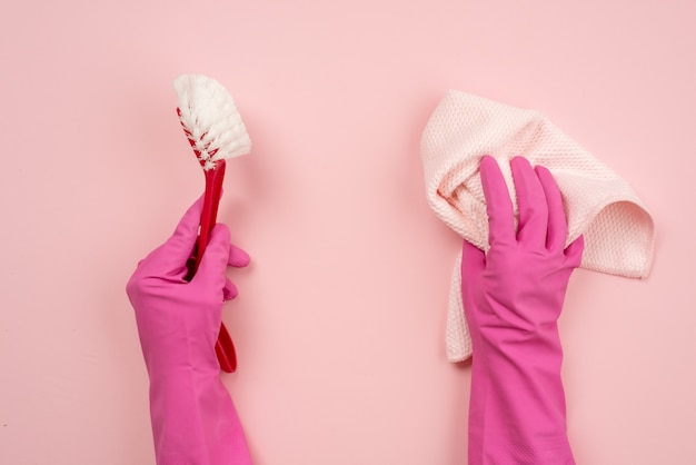 Closeup hands wearing in latex gloves holding a rag and household brush. top view
