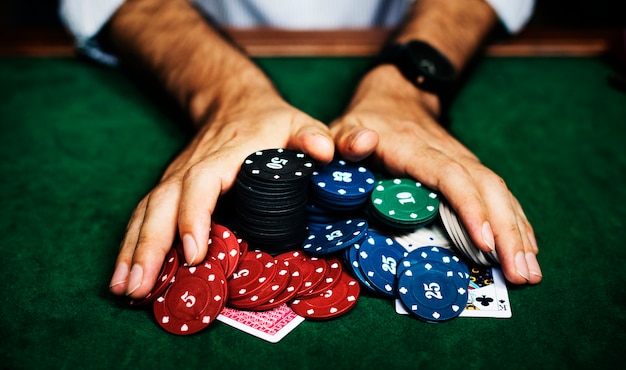 Closeup of hands with gambling tokens and card