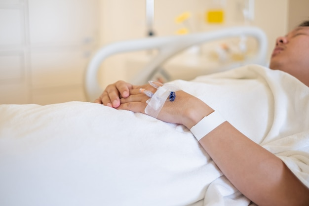 Closeup of hands with intravenous (iv) man patient in hospital bed.