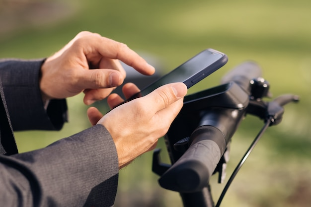 Closeup of hands with phone tourist taking escooter or bicycle phone application for rental scooter