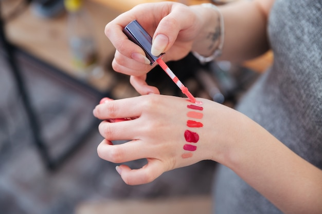 Closeup of hands of woman makeup artist testing lip gloss different colors on her hand