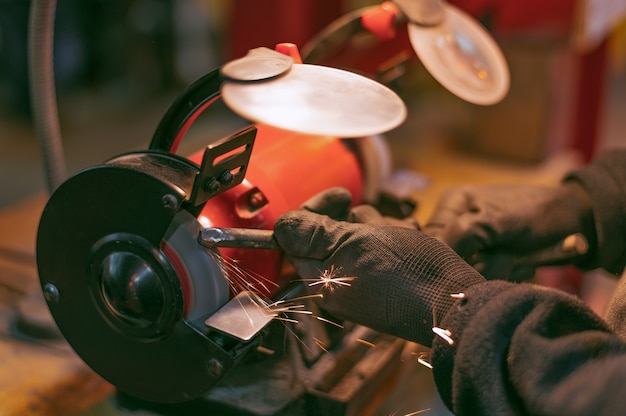 Closeup of the hands of a worker in black gloves working on a metal part on a red grinding machine