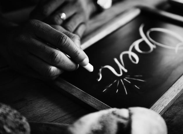 Closeup of hands writing open word on chalkboard