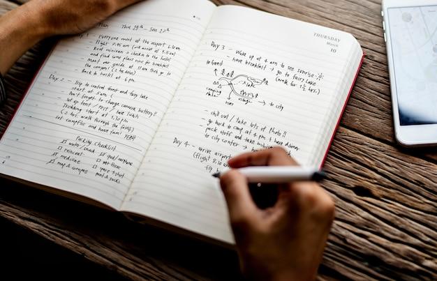 Closeup of hands writing travel plan
