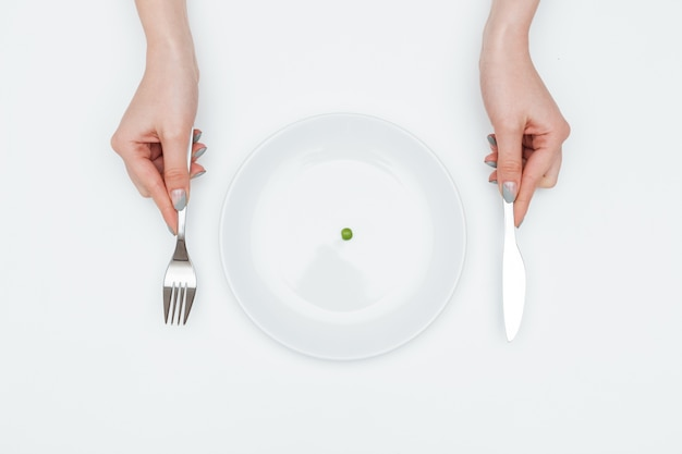 Closeup of hands of young woman eating one small green pea using knife and fork