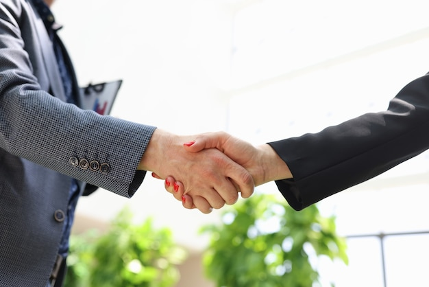 Closeup of handshake of business man and woman in suits in office