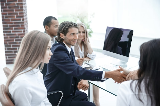 机の後ろに座っているcloseup.handshakeトレーディングパートナー。パートナーシップの概念