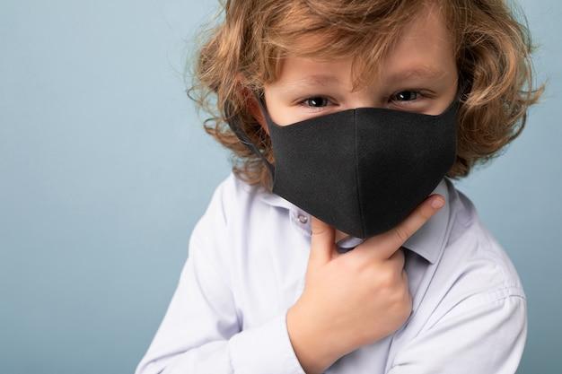 Closeup handsome curly blonde little boy in medical black mask standing