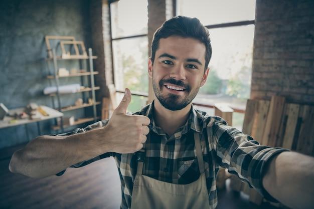 근접 촬영 잘 생긴 남자 마스터는 고객 목공 상점 차고 실내를 찾고 새로운 자신의 나무 비즈니스 산업 스튜디오에서 셀카 만들기 위로 엄지 손가락을 올리는